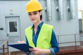 attractive engineer in safety vest and hardhat writing in clipboard