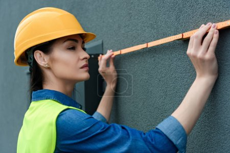 professional female architect in hardhat measuring wall