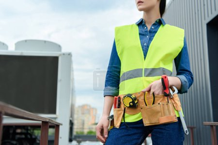 cropped view of female engineer with tool belt in safety vest
