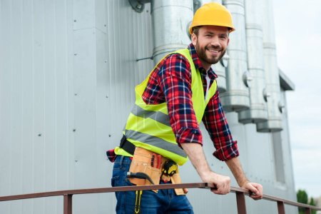 male professional architect in safety vest and helmet posing on roof