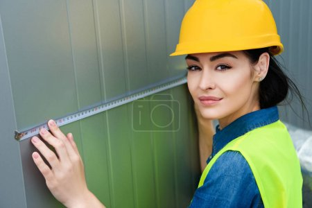 female architect in hardhat measuring metal wall