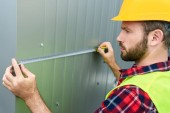 male professional constructor in helmet measuring wall