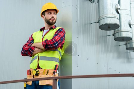 male professional engineer with tool belt posing with crossed arms at wall