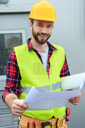 smiling engineer in safety vest and helmet working with blueprints