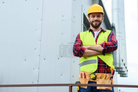 male professional engineer with tool belt posing with crossed arms