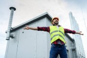 excited male professional constructor in safety vest and helmet posing with open arms on roof