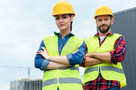 professional architects posing in helmets and safety vests with crossed arms