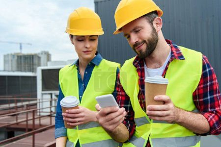 Photo for Engineers in helmets using smartphone on coffee break on roof - Royalty Free Image