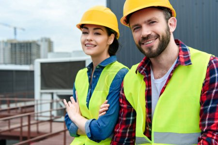 Photo pour Ingénieurs professionnels en hardhats et gilets de sécurité sur le toit - image libre de droit
