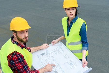 professional engineers in hardhats working with blueprints on roof