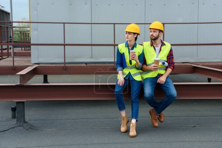 Photo pour Architectes masculins et féminins dans casques avec blueprint sur pause café assis sur le toit - image libre de droit