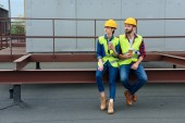 male and female architects in hardhats with blueprint on coffee break sitting on roof