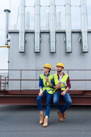 Photo pour Hommes et femmes ingénieurs casques avec blueprint sur pause café assis sur le toit - image libre de droit