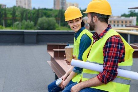 Foto de Arquitectos en cascos con blueprint en descanso sentado en el techo - Imagen libre de derechos