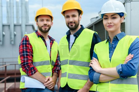professional engineers in safety vests and hardhats posing with crossed arms