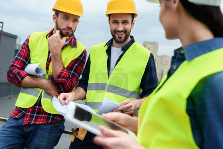 Photo for Engineers in safety vests and hardhats working with digital tablet and blueprints - Royalty Free Image