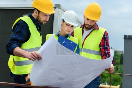 Photo for Professional engineers in hardhats working with blueprint and clipboard on construction - Royalty Free Image