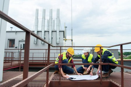 three engineers in helmets working with blueprints on roof together