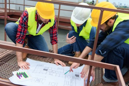 three architects in hardhats working with blueprints on roof