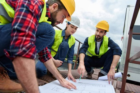 three engineers in hardhats working with blueprints on roof