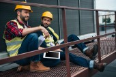 architects in hardhats with blueprints and digital tablet sitting on construction