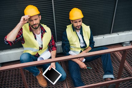 Photo for Architects with blueprints and digital tablet sitting on construction - Royalty Free Image