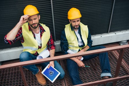engineers with blueprints and digital tablet with shazam website sitting on construction