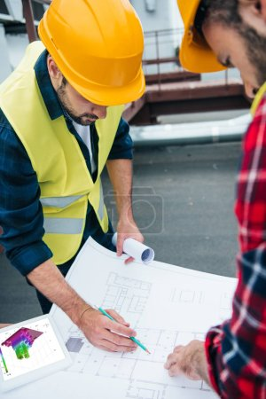 engineers in safety vests and hardhats with digital tablet drawing on blueprints