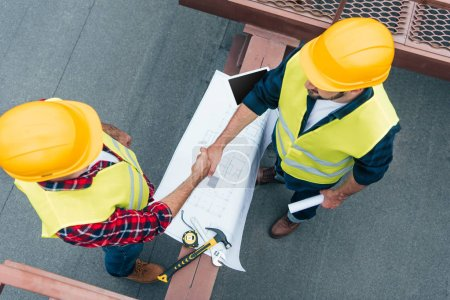 Photo for Overhead view of engineers in helmets with blueprints shaking hands on roof - Royalty Free Image