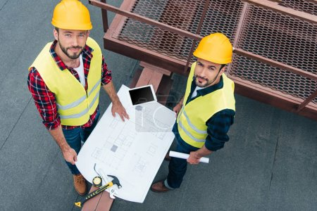 overhead view of male engineers in safety vests and helmets working with blueprints, digital tablet and tools on roof