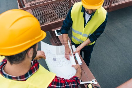 overhead view of architects in safety vests and helmets working with blueprints