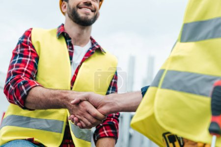 cropped view of engineers in safety vests shaking hands on roof