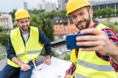 male engineers in safety vests and helmets with blueprints taking selfie on smartphone on roof