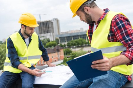 two engineers in helmets working with blueprints and clipboard on roof