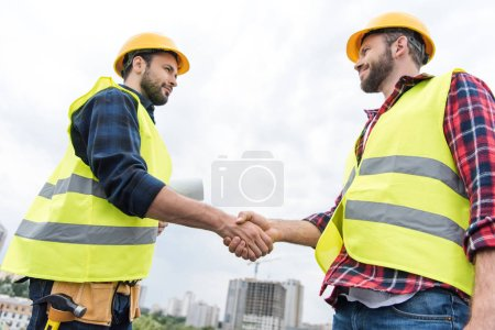 two engineers in safety vests and helmets shaking hands on roof