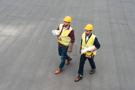 overhead view of architects in safety vests and hardhats with blueprints