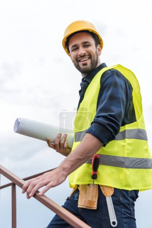 smiling engineer in safety vest with tool belt and blueprint