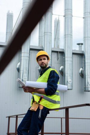 male engineer in safety vest and helmet with blueprint using digital tablet on construction