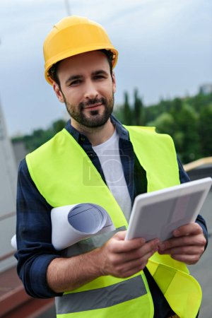 male engineer in safety vest and helmet holsing blueprint and digital tablet