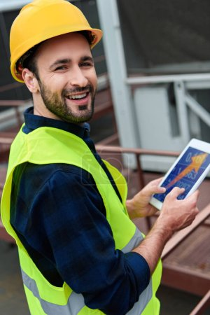 smiling architect in safety vest using digital tablet with arrow