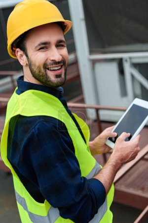 cheerful construct worker in safety vest and helmet using digital tablet with blank screen