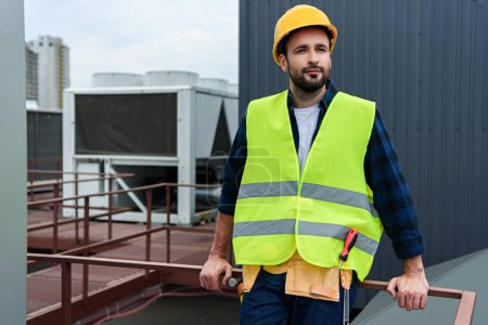 male architect in safety vest and hardhat with tool belt standing on roof