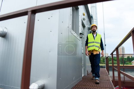 male engineer in safety vest and helmet with tool belt walking on roof