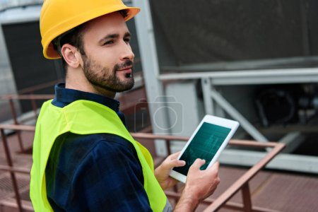 male engineer in safety vest and helmet using digital tablet with graphs