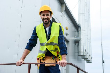 Photo for Male smiling engineer in safety vest and helmet with tool belt on construction - Royalty Free Image