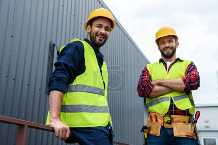 two architects in safety vests and hardhats standing on construction