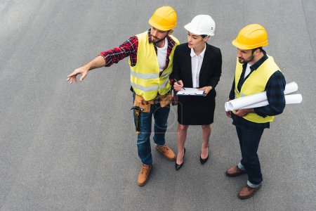Photo for Overhead view of female engineer and male workers with clipboard and blueprints pointing at construction - Royalty Free Image