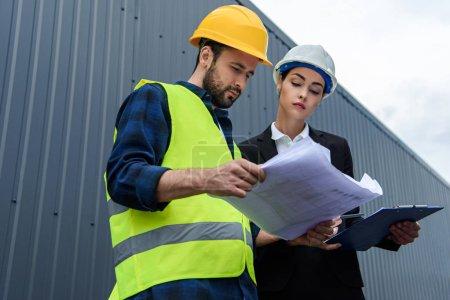 Photo pour Femme ingénieur et travailleur masculin dans des casques avec des plans sur la construction - image libre de droit