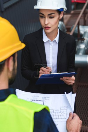 selective focus of architect and worker in helmets with blueprint and clipboard on construction