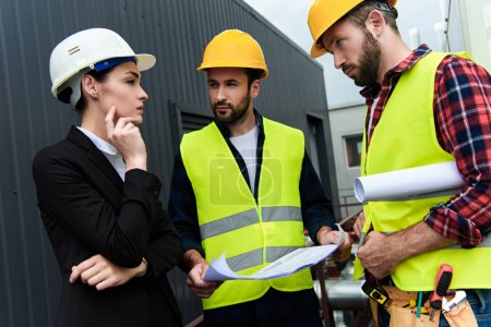 female engineer and male workers with blueprints talking on construction